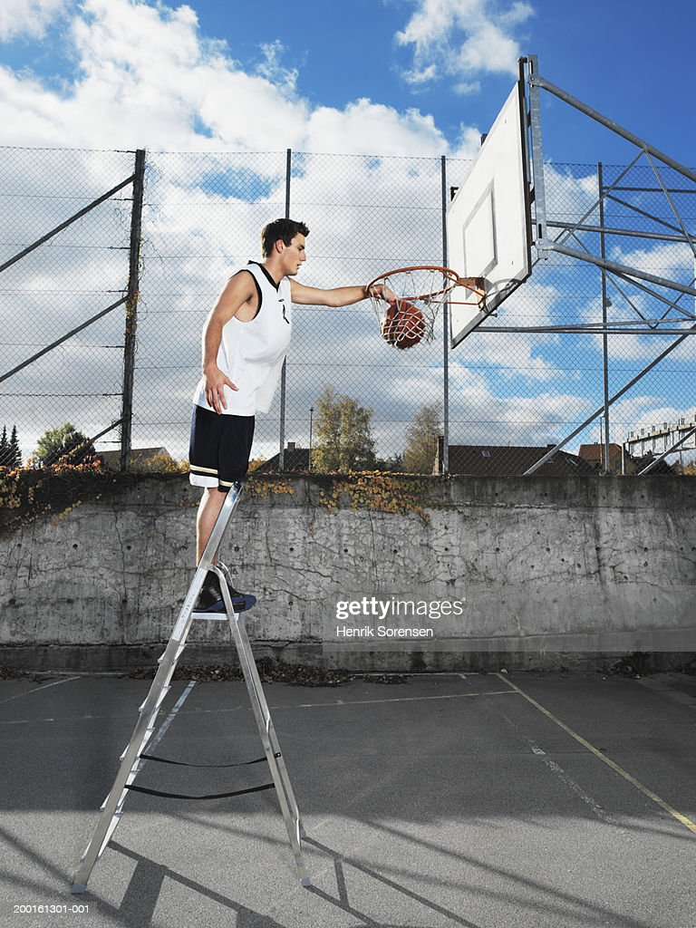 Young man on step ladder, dunking basketball in hoop, side view