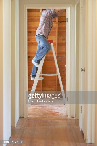 Young man on step ladder in house, side view, low section
