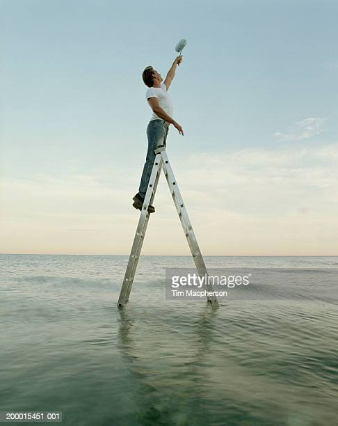Young man on step ladder in sea holding up paint roller