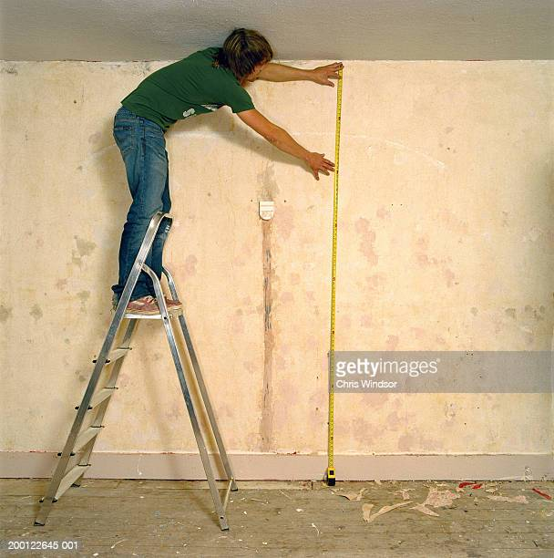 Young man on stepladder holding tape measure against wall, side view