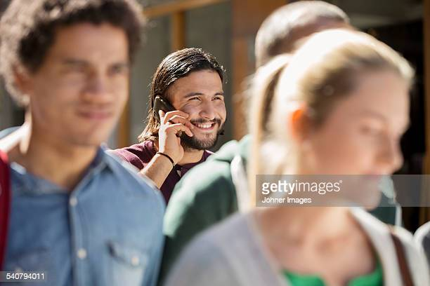 Young man on street talking via cell phone