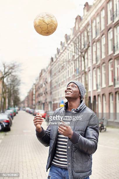 Young man on street throwing soccer ball, Amsterdam, Netherlands