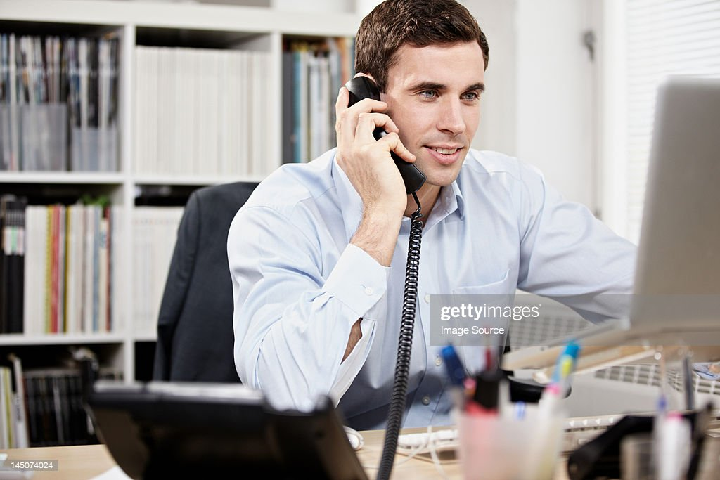 Young man on telephone and working on laptop : Stock Photo