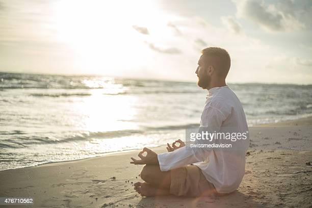 Young man on the beach exercising yoga