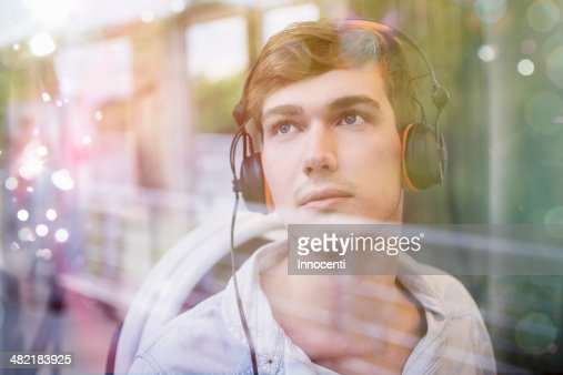 Young man on train, daydreaming and listening to headphones