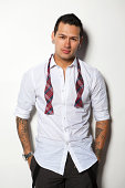 Young man on white with tattoos in dress attire