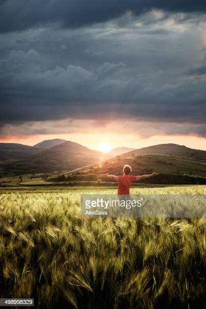 Jovem ao ar livre com as mãos levantadas enjoing o pôr-do-sol