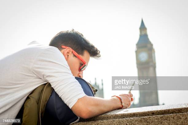 Young man outdoors, leaning on wall, looking at smartphone, Big Ben in background, London, England, UK