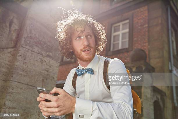 Young man outdoors, using smartphone, wearing shirt and bow tie