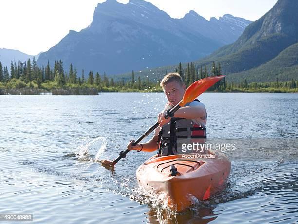 Young man paddles kayak on mountain lake