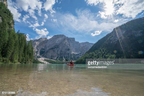 Young man paddling red canoe on lake Braies, Italy