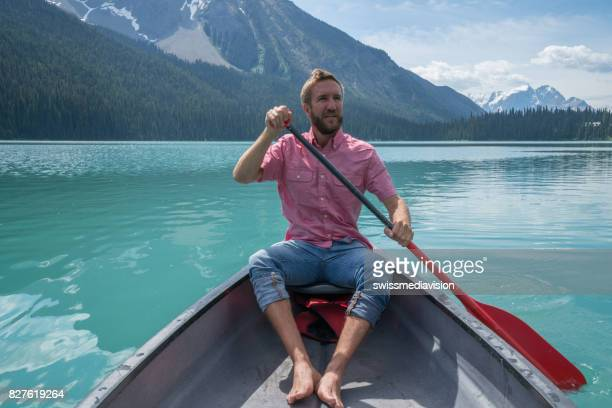 Young man paddling red canoe on turquoise lake