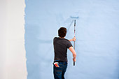 Young man painting a wall