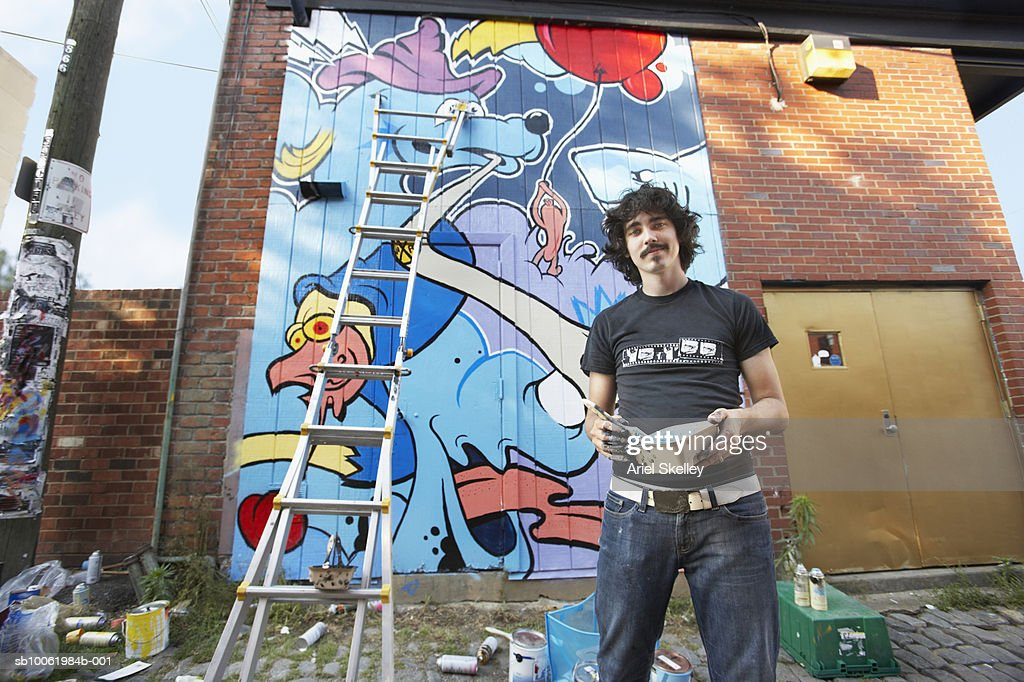 Young man painting mural on wall, portrait : Stock Photo