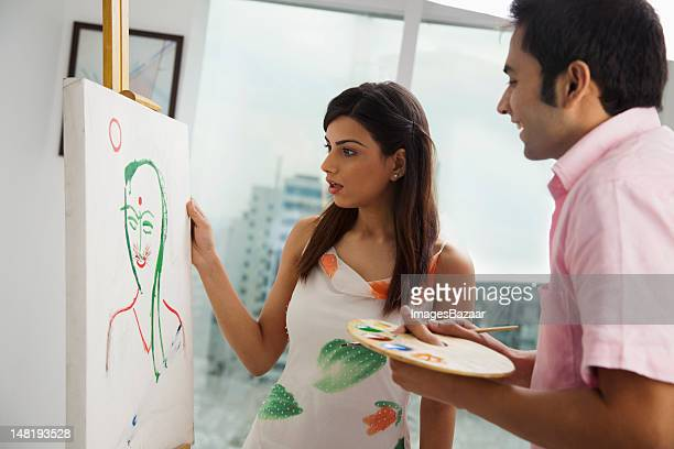 Young man painting to his girlfriend