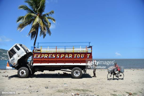 A young man paints a truck next to the sea in CapHaitien on September 6 240 km from PortauPrince Inhabitants of Shada a poor riverside community in...