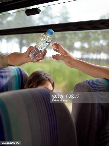 Young man passing water bottle to young woman on coach