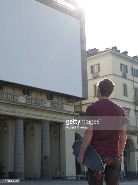 Young man pauses to look at empty billboard