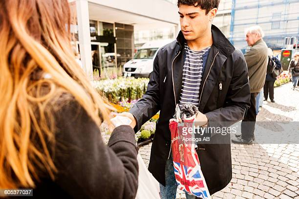 Young man paying cash to female vendor while standing in market
