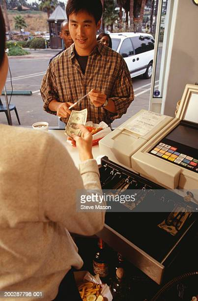 Young man paying for order in fast food restaurant