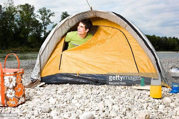 young man peeking through tent in the morning