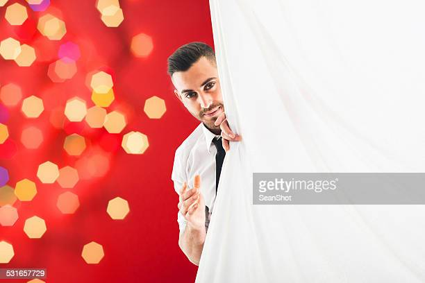 Young Man Peeping Through Curtain