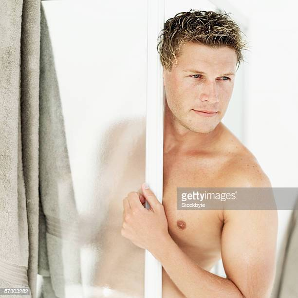 Young man peering out of the shower