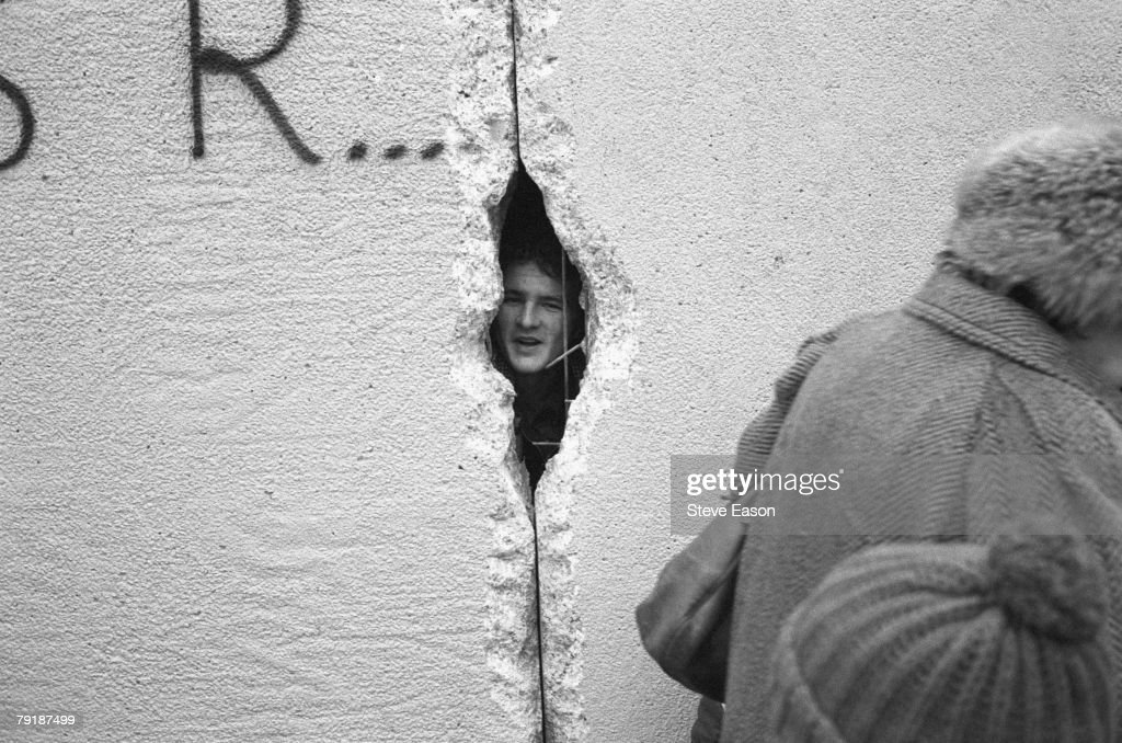 A young man peers into East Berlin though a hole in the Berlin Wall at the effective end of the city's partition, 31st December 1989.