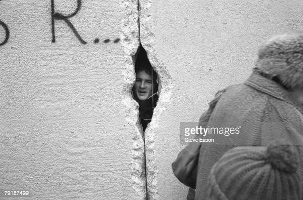 A young man peers into East Berlin though a hole in the Berlin Wall at the effective end of the city's partition 31st December 1989