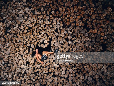 Young man perching on stack of logs : Stock Photo