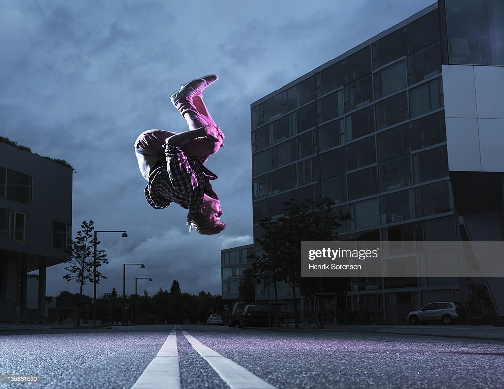 young man performing a jump in urban environment : Stock Photo