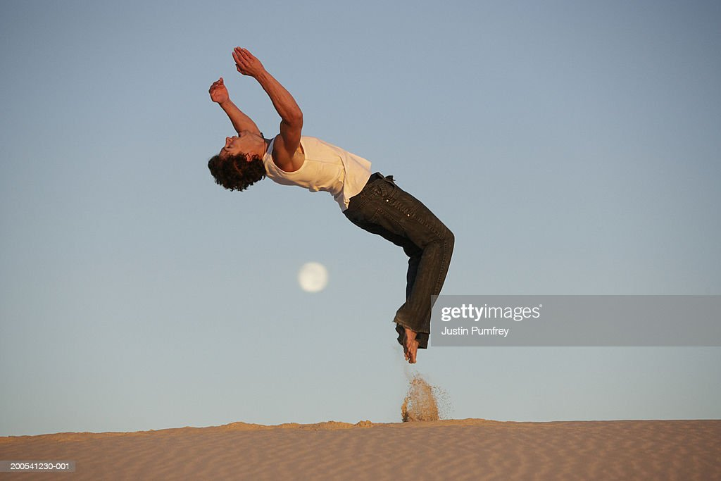 Young man performing backflip in desert, side view, dusk : Stock Photo