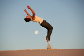 Young man performing backflip in desert, side view, dusk