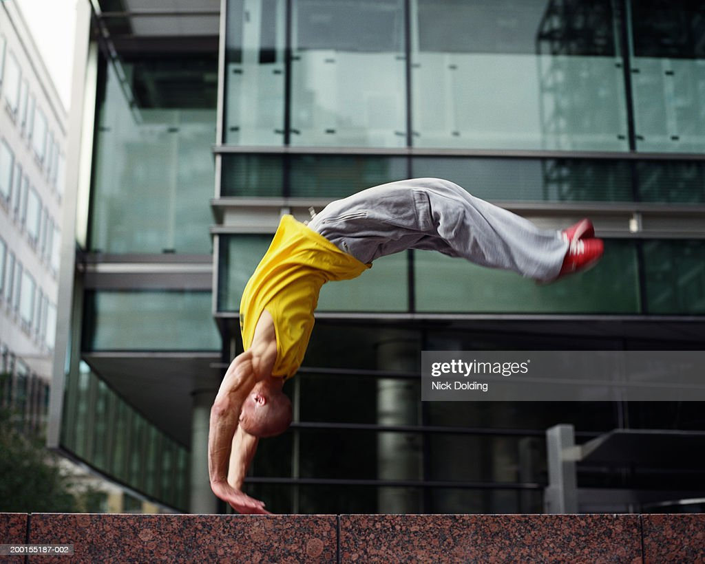 Young man performing backflip on wall outdoors (blurred motion) : Stock Photo