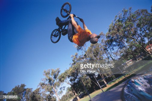 Young man performing bike stunt on ramp : Stock Photo