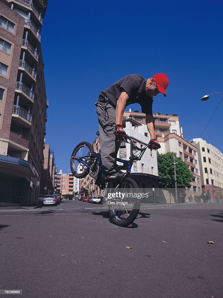 Young man performing bike stunt on street : Stock Photo