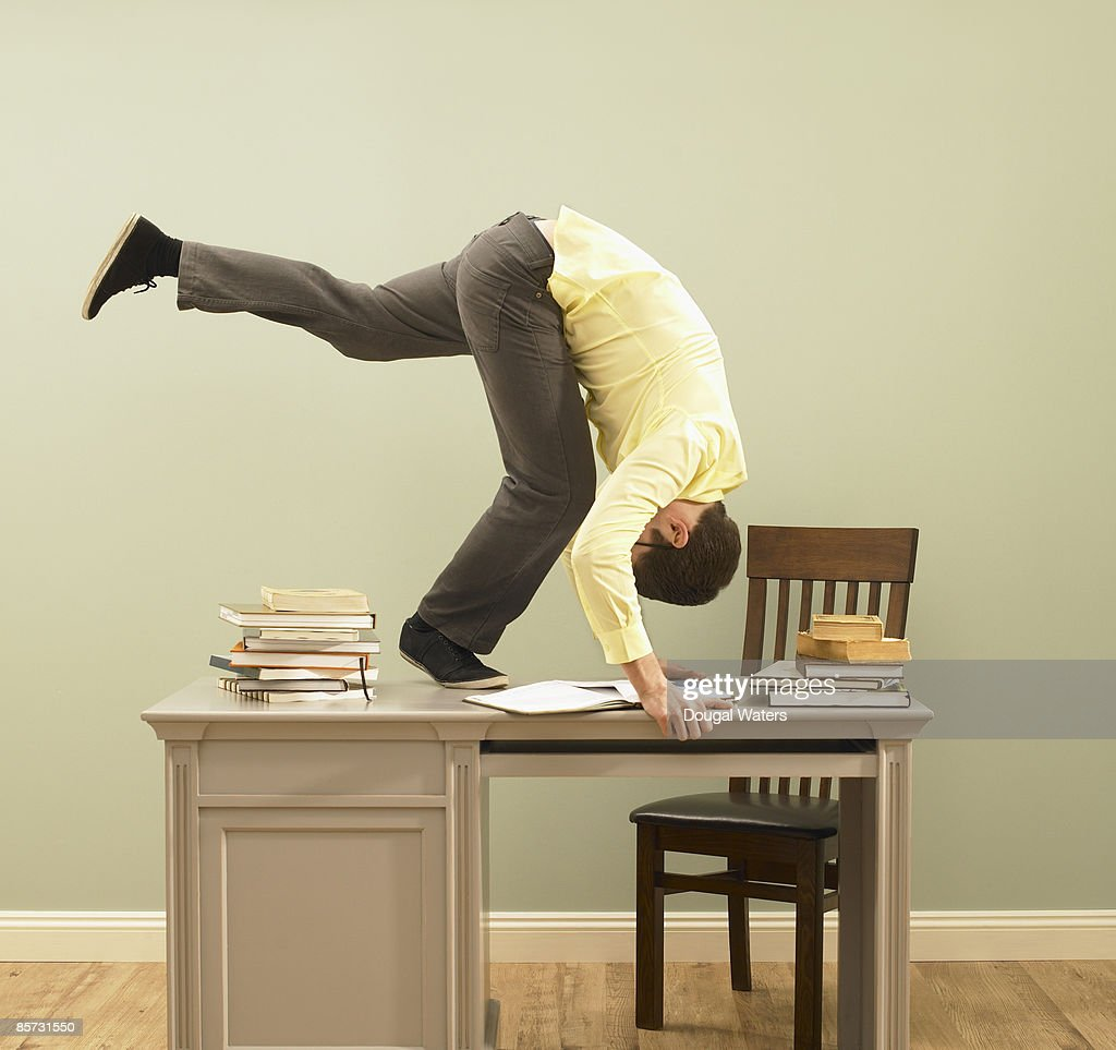 Young man performing forward roll on desk.