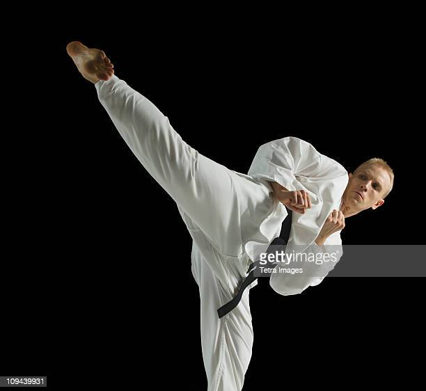 Young man performing karate kick on black background