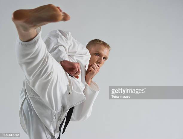 Young man performing karate kick on white background