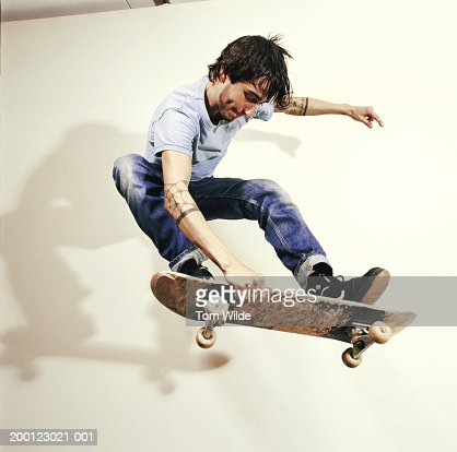 Young man performing skateboard trick, mid-air