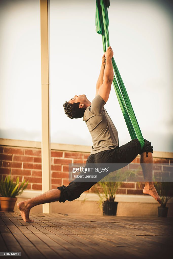 A young man performs aerial yoga.