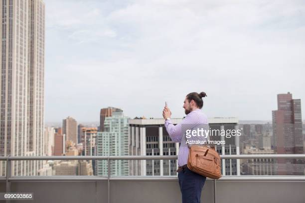 Young man photographing city view while standing at rooftop restaurant
