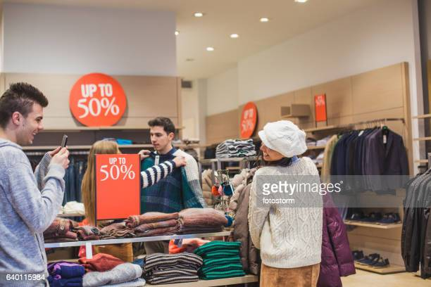Young man photographing his girlfriend while shopping