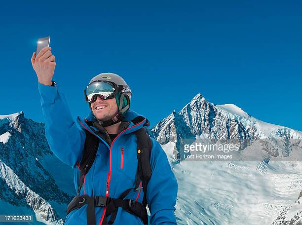 Young man photographing self on smartphone in mountains