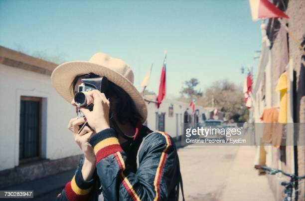 Young Man Photographing While Standing Against Sky On Sunny Day