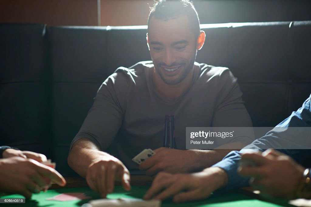 Young man picking up card game winnings at pub card table