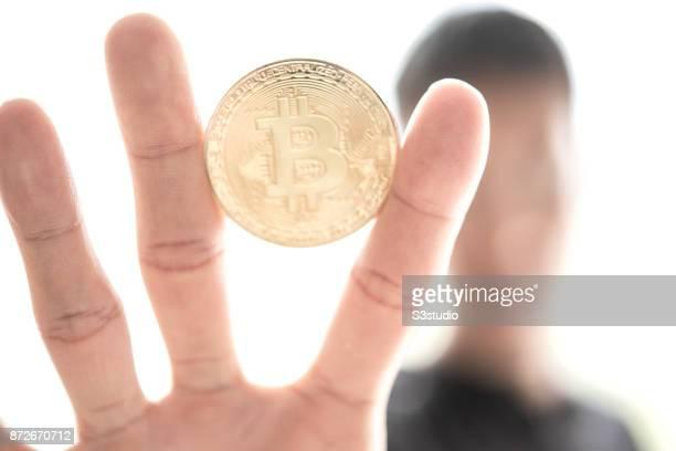 Young man playing a visual representation of the digital Cryptocurrency Bitcoin with US Dollar on November 9 2017 in Hong Kong Hong Kong...