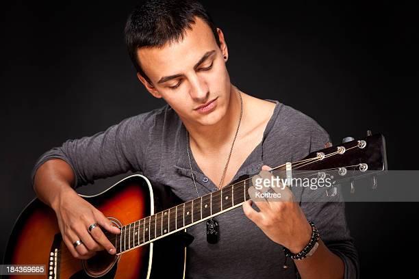 Jeune homme jouant de la guitare acoustique