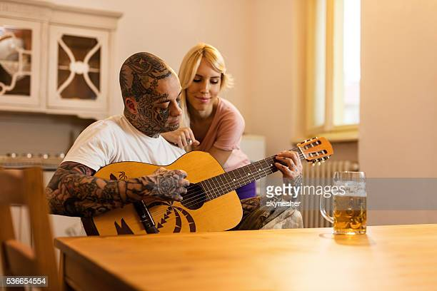 Young man playing acoustic guitar to his girlfriend at home.