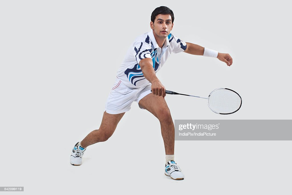 Young man playing badminton isolated over gray background